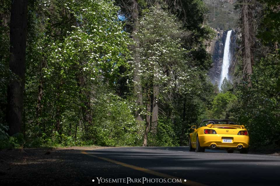 Yellow convertible driving under Bridalveil Fall on Southside Drive.