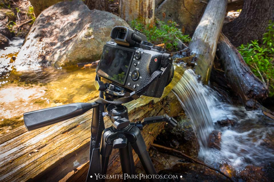 Mirrorless camera + tripod capturing long exposure creek waterfall