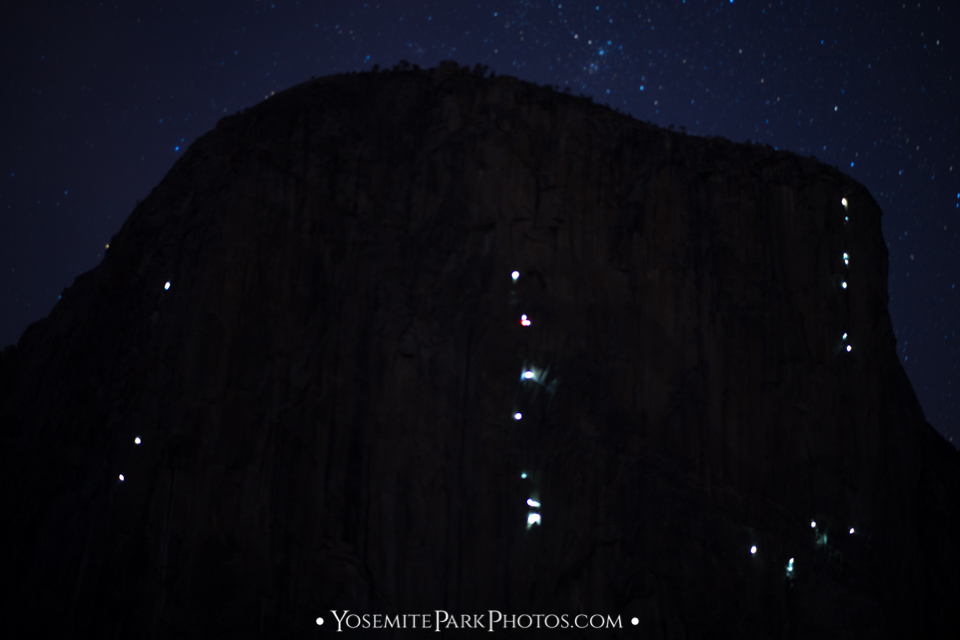 Rock climbers camping on the side of El Capitan, with lantern lights and milky way stars