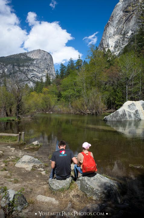 Hiker couple sitting at edge of Mirror Lake, with North Dome in distance