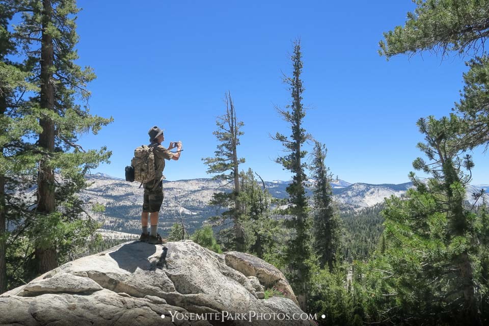 Hiker taking picture at viewpoint- May Lake Hike Photos