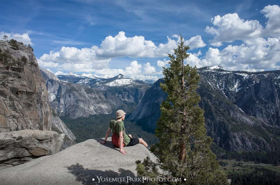 Lone hiker man sitting at sweeping valley view- Yosemite Hikers