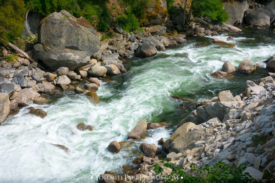 Rapids emptying into an emerald pool with large river boulders.