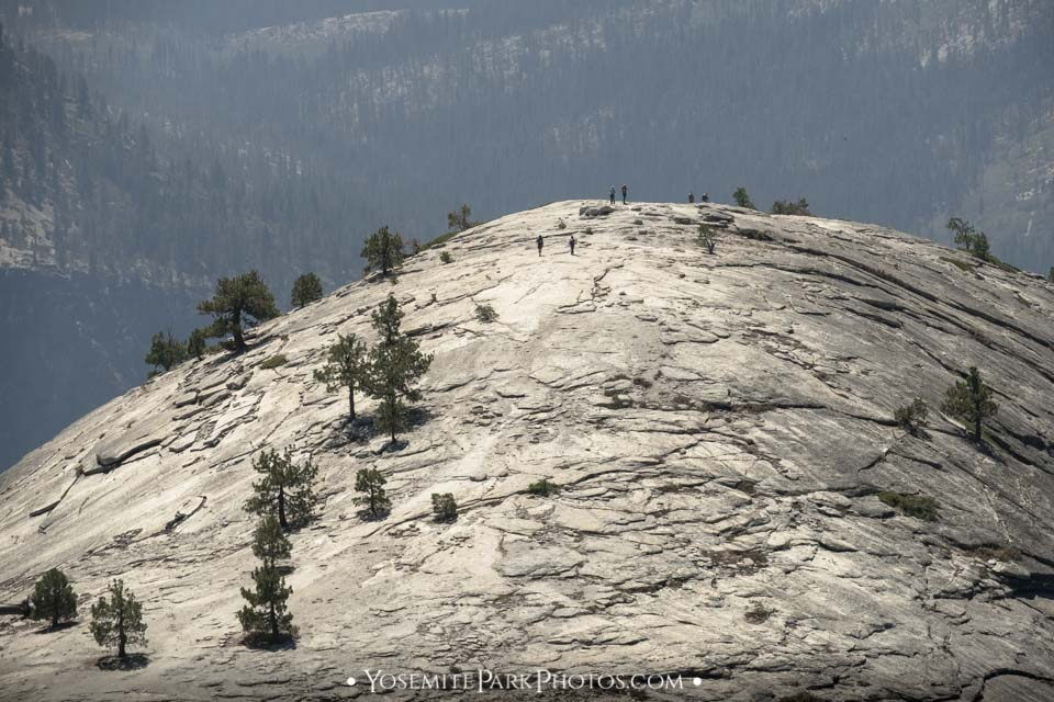 Hikers climbing to the top of North Dome