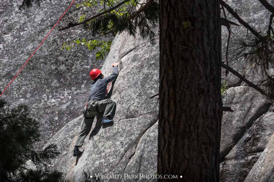 Man doing an ascent with ropes & safety harness - Yosemite rock climbers