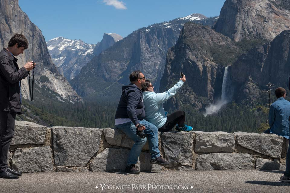 Couple taking a photo, sitting on ledge at Tunnel View - tourist selfies